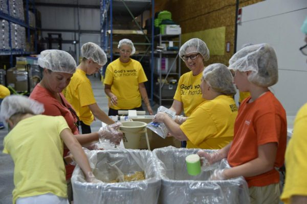 Youth and adults packing food